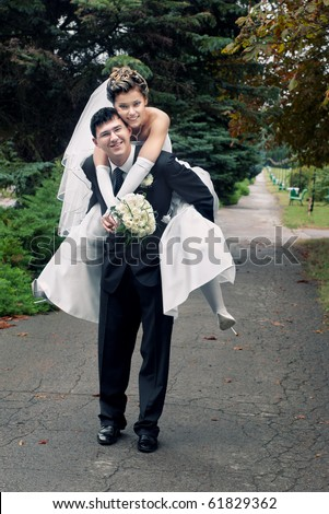 Smiling groom carrying on his back bride outdoors in park with selective focus