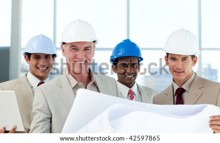 Smiling group of architect examining blueprints in a building