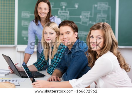 Smiling group of attractive teenage students in a college classroom sitting at a table with their laptops with a female teacher standing at the end