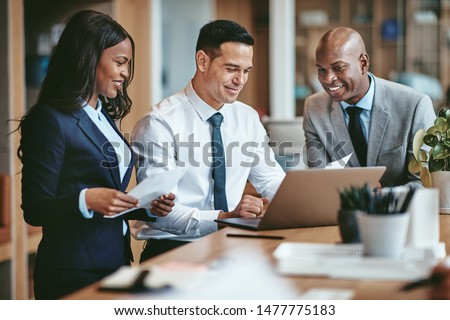 Smiling group of diverse businesspeople going over paperwork together and working on a laptop at a table in an office