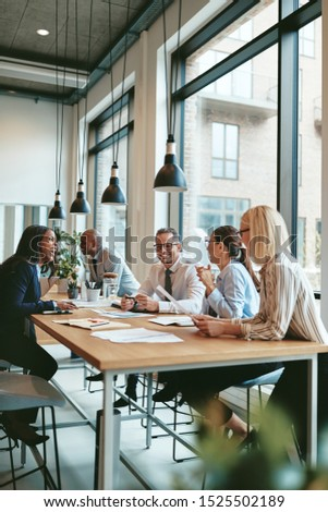 Smiling group of diverse businesspeople going over paperwork together during a meeting around a table in a modern office