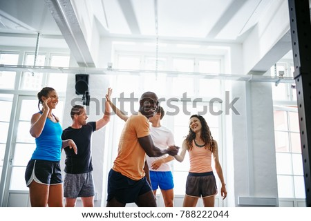 Smiling group of diverse friends standing in a gym enthusiastically celebrating together after working out