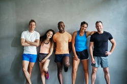 Smiling group of friends in sportswear laughing while standing arm in arm together in a gym after a workout