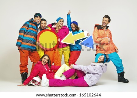 Smiling group of friends wearing snowboard costumes