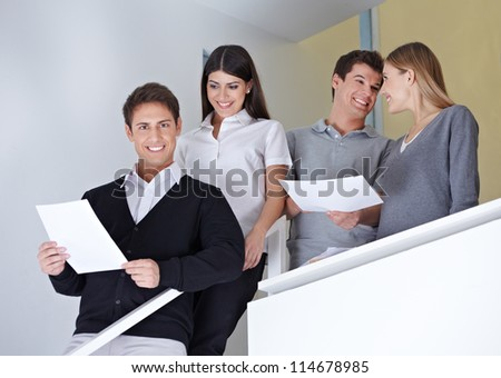 Smiling group of happy business people standing on stairway