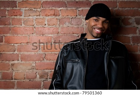 Smiling guy dressed in black near a brick wall.