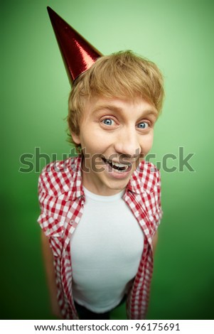 Smiling guy in a celebrating cone cap looking excitedly at camera, fool's day series or birthday