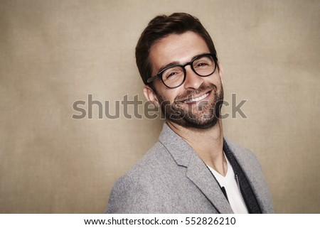 Smiling guy in glasses wearing grey coat