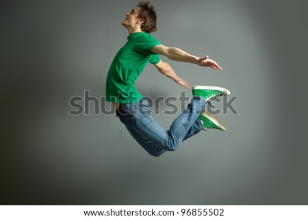 Smiling guy jumping high holding hands behind #96855502