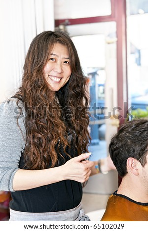 Smiling hairdresser cutting hair in her salon