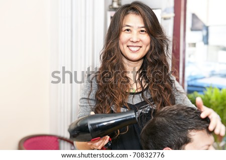 Smiling hairstylist drying hair with hairdryer in her salon
