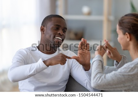 Smiling handsome African American man and woman speaking sign language close up, deaf friends or couple communicating, having fun, pleasant conversation, sitting together on couch at home Stock foto ©