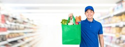 Smiling handsome Asian man holding grocery shopping bag in supermarket banner background with copy spce for food delivery service concept