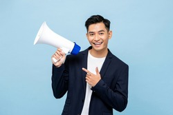 Smiling handsome Asian man holding megaphone in light blue isolated background