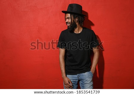 Smiling handsome attractive young african american man guy with dreadlocks 20s wearing black casual t-shirt hat posing looking aside isolated on bright red color wall background studio portrait Stock photo ©