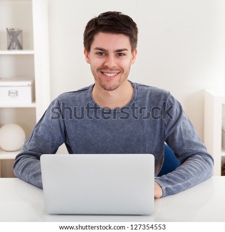 Smiling handsome casual young man sitting at a table using a laptop in a home office