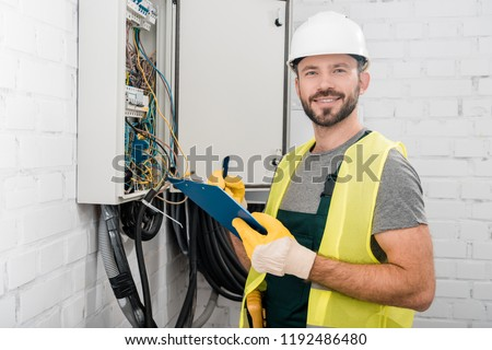 smiling handsome electrician holding clipboard near electrical box in corridor and looking at camera