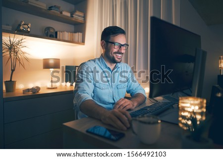Smiling handsome freelancer working remotely from home at night.