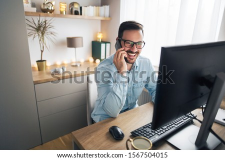 Photo of Smiling handsome freelancer working remotely from home. He is speaking on the phone.
