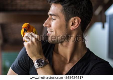 Smiling handsome man feeding parrot sitting on his shoulder. Horizontal indoors shot