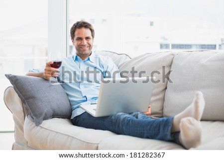 Smiling handsome man relaxing on sofa with glass of red wine using laptop at home in the living room