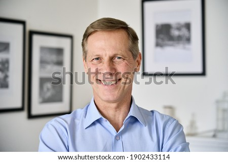 Smiling handsome middle aged 50s single man looking at camera standing at home, happy satisfied confident senior mature european male model posing indoors for close up face headshot portrait.