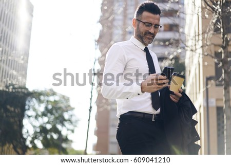 Smiling handsome office worker in corporate clothing with cup of take away coffee sending text message to friends using smartphone and high speed internet technology.Copy space area for your advertise #609041210