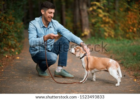 smiling handsome owner stroking dog, full length side view photo.animal lover