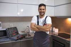 Smiling handsome plumber standing with crossed arms and looking at camera in kitchen. Portrait of a repairman on the kitchen. Service Industry: Mid-adult repairman working at customer's home.