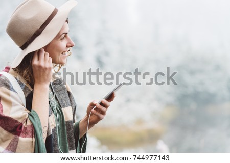 Smiling handsome woman listening music with her mobile phone in first snow. Traveling among stunning winter landscape. Vacations in mountain wilderness. Wanderlust and boho style #744977143