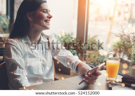 Shutterstock Smiling handsome woman reading news from internet using mobile phone, breakfast in cafe