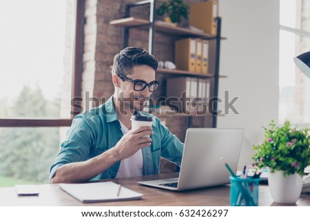 Smiling handsome worker in glasses drinking coffee while watching video on his laptop at office #632426297