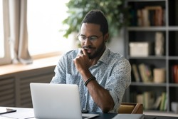 Smiling handsome young african american guy in glasses sitting at table, looking at computer screen. Focused millennial biracial man working on project in modern office or studying online at home.