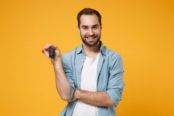 Smiling handsome young man in casual blue shirt posing isolated on yellow orange wall background, studio portrait. People sincere emotions lifestyle concept. Mock up copy space. Hold in hand car keys