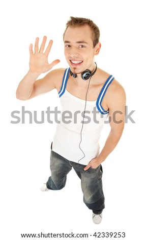 Smiling handsome young man in casual style with headphones shows hello by his hand, isolated on white background