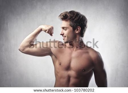Smiling handsome young man showing his biceps