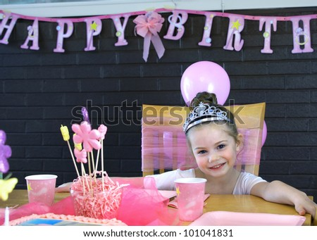 Smiling happily, little girl poses at her birthday party.  She is sitting at the table with cup and decorations.