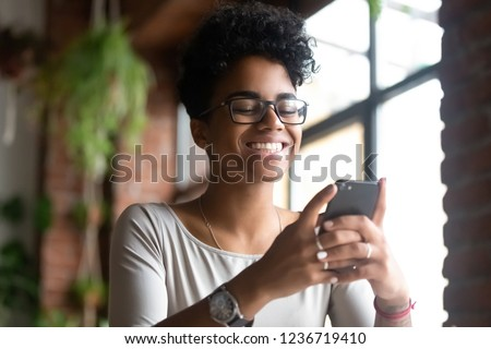 Smiling happy African American woman using phone, browsing mobile apps or websites, get good message from friend or boyfriend, check social network, looking at smartphone screen, reading good news