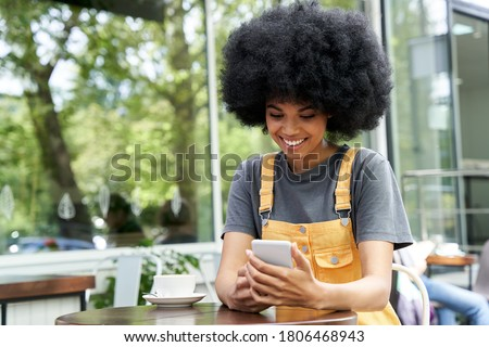 Smiling happy African American young hipster mixed race gen z young woman with Afro hair holding smart phone, checking social media, using mobile app sitting at outdoor table in cozy modern cafe.