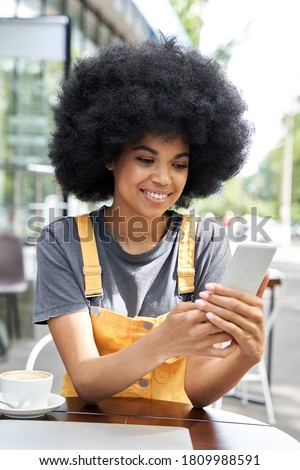 Smiling happy African American young hipster mixed race gen z young woman with Afro hair holding smart phone device, using mobile app sitting at outdoor table in modern city cafe. Vertical view