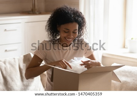 Smiling happy african athnicity young woman sitting on couch in living room, unpacking carton box parcel online order from international internet store, satisfied with fast safe air delivery service.