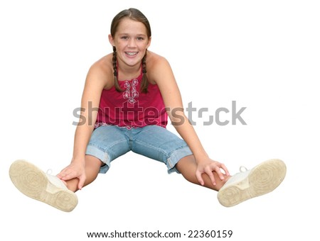 Smiling, happy, approachable teen or preteen girl sitting on  a path in a park, outdoors