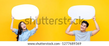 Smiling happy Asian couple with blank speech bubbles on colorful yellow banner background