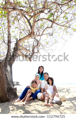 smiling happy asian family at the beach together