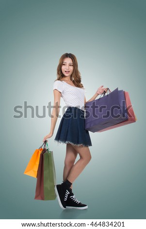 Smiling happy Asian woman shopping and holding bags, full length portrait isolated. #464834201