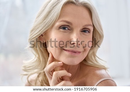 Smiling happy attractive 50s middle aged mature blond woman, old lady looking at camera advertising anti age face skin and body care treatment cosmetics posing in bathroom. Close up headshot portrait