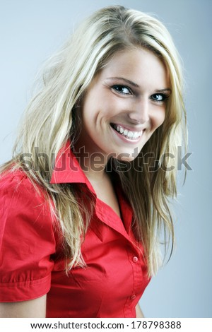 Smiling happy beautiful blond woman in a red blouse looking at the camera with a beaming joyful smile on a grey background