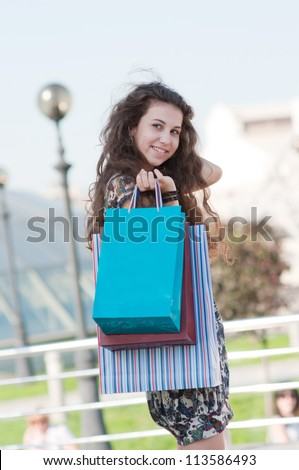 Smiling, happy, beautiful girl with shopping bags