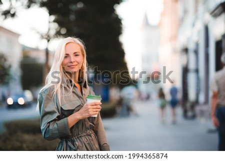 Smiling happy beautiful girl 20-24 year old drinking coffee walking on city street outdoors. Looking at camera. 20s.  Foto stock ©