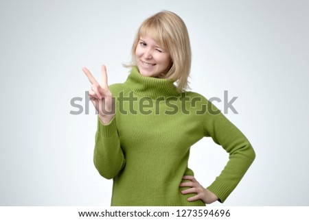 Smiling happy blonde woman in freen sweater showing victory sign and looking at camera